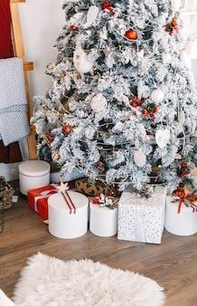 Mooie kerstboom met geschenkdozen in helder witte woonkamer.