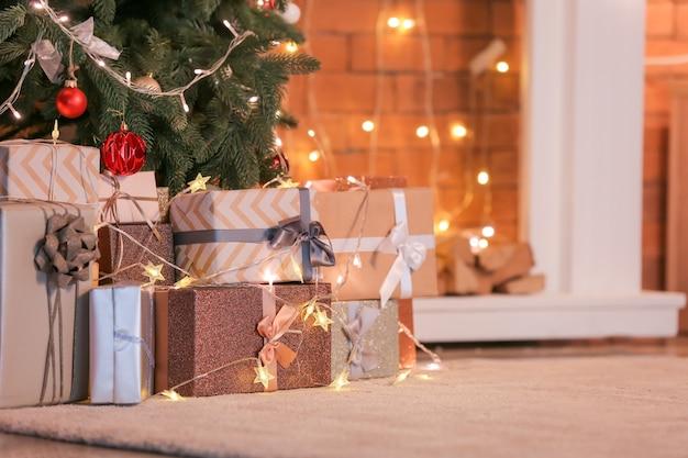 Mooie kerstcadeaus onder dennenboom op de vloer in de kamer