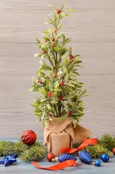 Mooie kerstcompositie met maretakplant op houten vloer