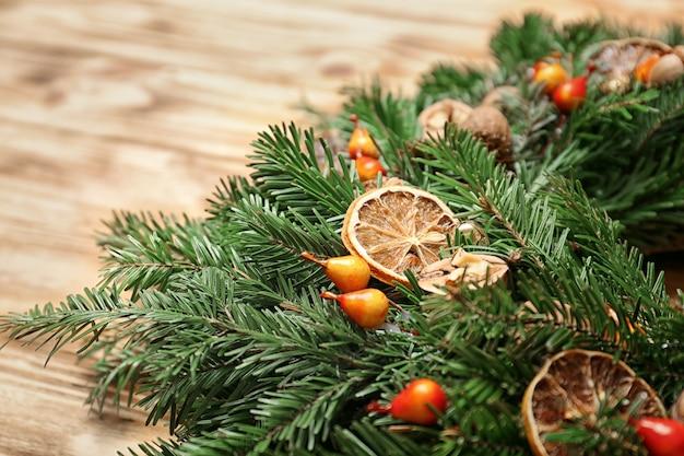 Mooie kerstkrans gemaakt door professionele bloemist op houten ondergrond, close-up