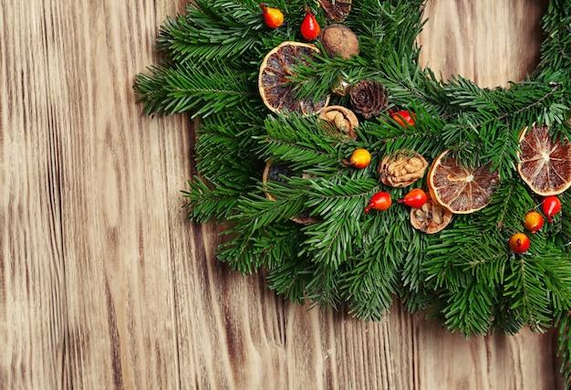 Mooie kerstkrans gemaakt door professionele bloemist op houten ondergrond