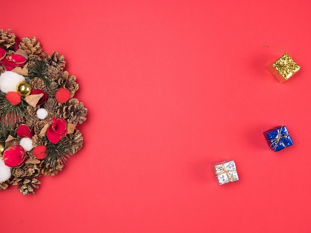 Mooie kerstkrans met kleine geschenkdozen op rode achtergrond. feestelijk interieur