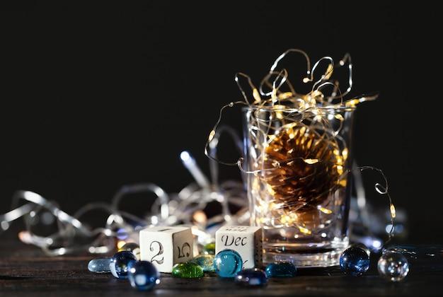 Mooie kerstmisachtergrond met blokkalender en gloeiende kerstmislichten in een glaskruik.