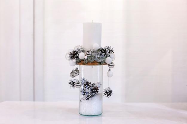 Mooie kerstversiering met kaars gemaakt door professionele bloemist op lichte achtergrond