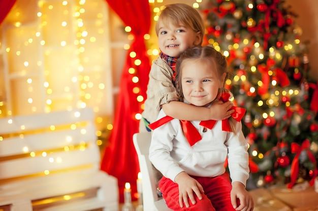 Mooie kinderen broer en zus op kami achtergrond met kerstverlichting en kerstboom versierd met garland
