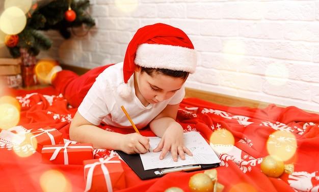 Mooie kinderen in hoed schrijven thuis kleine kerstman schrijft een brief