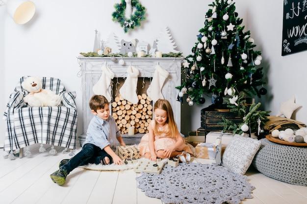 Mooie kinderen spelen in de kamer met cristmas boom en open haard. wintervakantie concept.