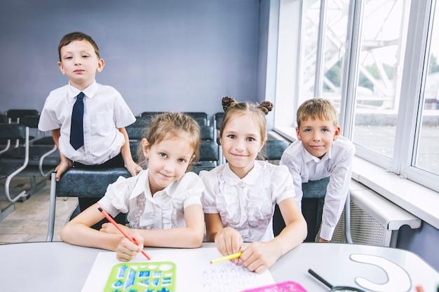 Mooie kinderen zijn leerlingen die samen in een klaslokaal op school gelukkig onderwijs krijgen Premium Foto