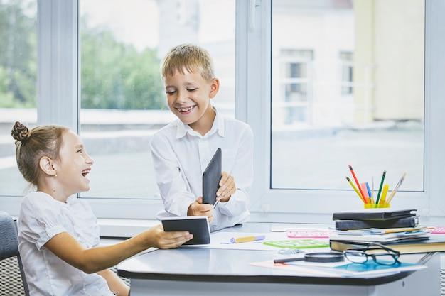 Mooie kinderen zijn studenten samen in een klaslokaal op school krijgen onderwijs met tablets gelukkig