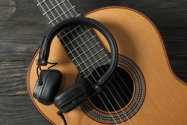 Mooie klassieke gitaar met koptelefoon op houten tafel, close-up