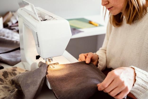 Mooie kleermakersvrouw die naaimachine met behulp van