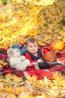 Mooie kleine baby die op een picknickdeken legt