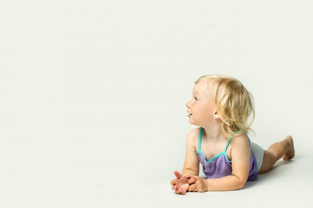Mooie kleine baby lacht, op zoek naar de kant terwijl liggend op haar buik