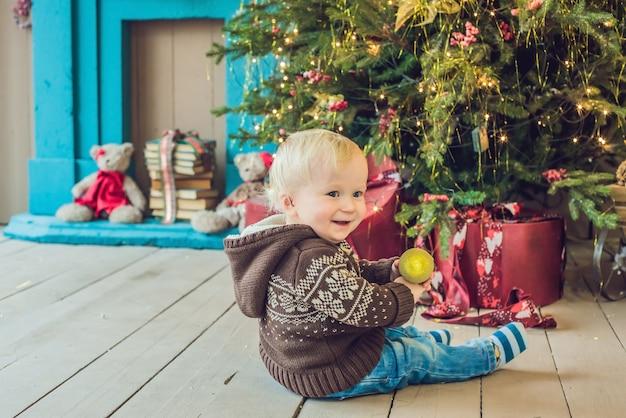 Mooie kleine baby viert kerstmis in een kerstkostuum