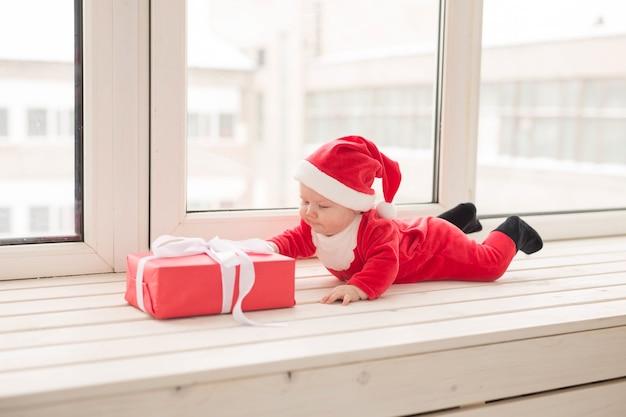 Mooie kleine baby viert kerstmis. nieuwjaarsvakantie. baby in een kerstkostuum en in een kerstmuts.