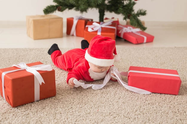 Mooie kleine baby viert kerstmis. nieuwjaarsvakantie. baby in een kerstkostuum en in kerstmuts en geschenkdoos, bovenaanzicht.