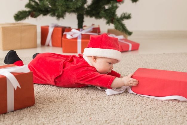 Mooie kleine baby viert kerstmis. nieuwjaarsvakantie. baby in kerstkostuum en in kerstmuts en geschenkdoos.
