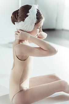 Mooie kleine ballerina die een wit zwaanverband op haar hoofd draagt