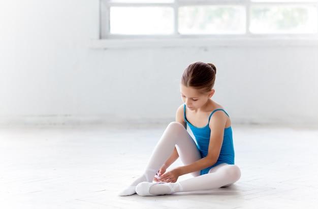 Mooie kleine ballerina in blauwe jurk om te dansen en te voet pointe-schoenen te zetten