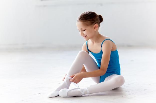 Mooie kleine ballerina in blauwe jurk om te dansen te voet pointe schoenen te zetten