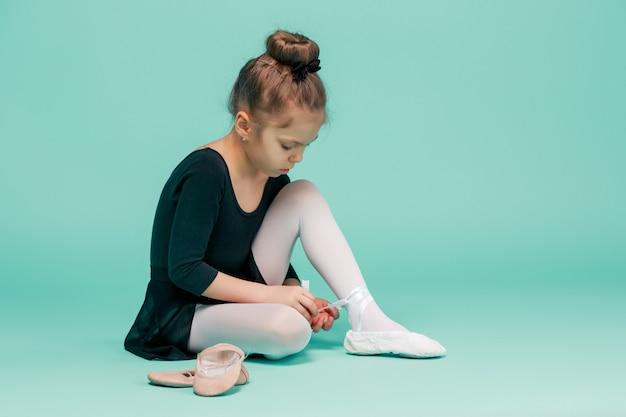 Mooie kleine ballerina in zwarte jurk om te dansen en te voet pointe-schoenen te zetten
