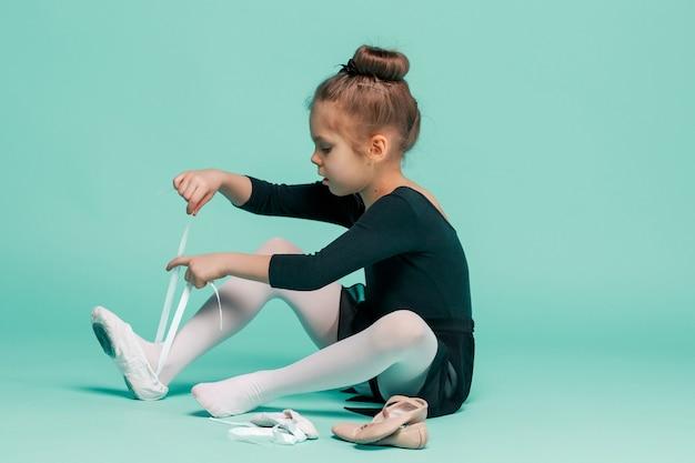 Mooie kleine ballerina in zwarte jurk voor dansen zetten voet pointe-schoenen