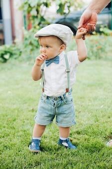 Mooie kleine blanke jongen in stijlvolle kleding loopt met ouders naar de tuin