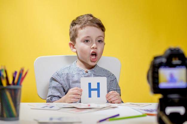 Mooie kleine blogger bloeit over het leren van het alfabet op geel. terug naar school. online onderwijs op afstand.