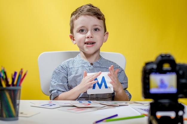 Mooie kleine blogger bloeit over het leren van het alfabet op gele achtergrond