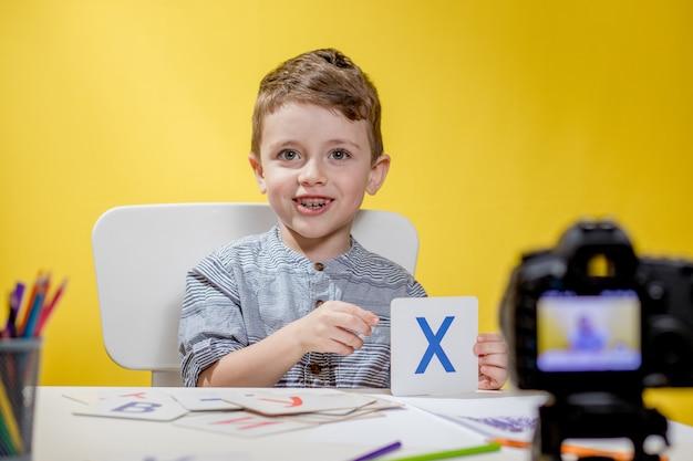 Mooie kleine blogger bloeit over het leren van het alfabet