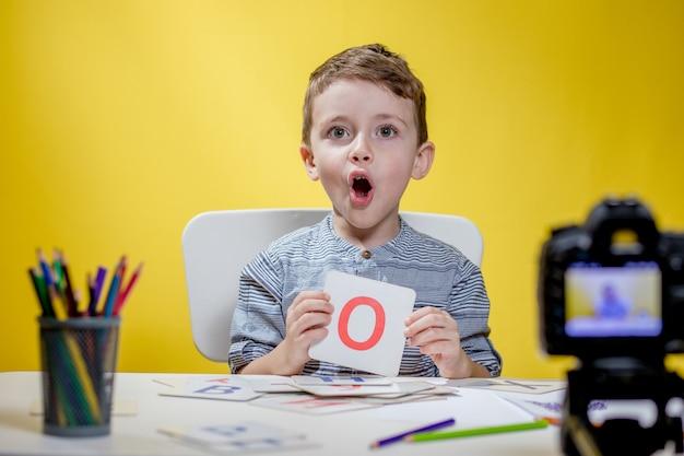 Mooie kleine blogger die blogt over het leren van het alfabet op geel. terug naar school. online onderwijs op afstand.