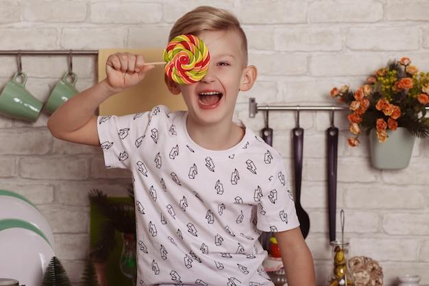 Mooie kleine blonde jongen zit op de keukentafel met een grote lolly in zijn hand. jong geitje dat gezicht behandelt met groot suikergoed en zijn brede glimlach toont