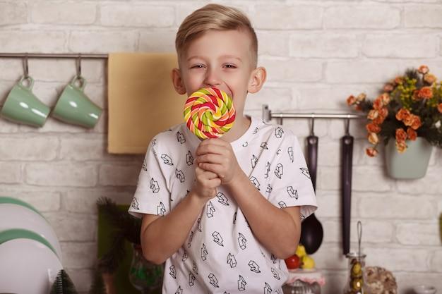 Mooie kleine blonde jongen zit op de keukentafel met een grote lolly in zijn hand