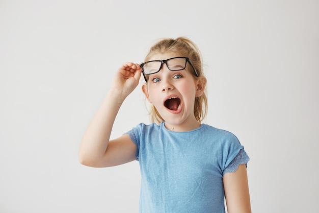 Mooie kleine blonde juffrouw met grote blauwe ogen en licht haar dwaas poseren met wijd geopende mond en het verhogen van haar bril met de hand.