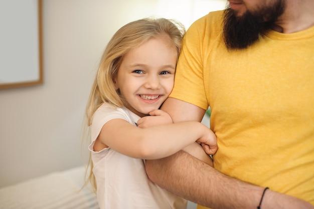 Mooie kleine blonde meisje lachend terwijl de hand van haar vader thuis in de ochtend omhelst.