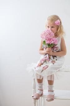 Mooie kleine blonde meisjes met roze bloemen op witte achtergrond