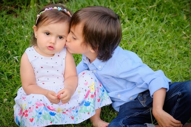 Mooie kleine broertjes zitten in de wei. broer geeft zijn zus een kus.