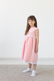 Mooie kleine brunette meisje in een roze jurk poseren op een witte muur. het concept van schattige kinderen. advertentie ruimte