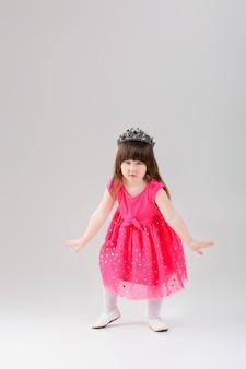 Mooie kleine brunette meisje in roze prinses jurk met een kroon die probeert te buigen op een grijze achtergrond. schattige baby