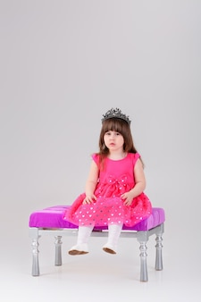 Mooie kleine brunette meisje in roze prinses jurk met kroon zittend op een roze stoel op grijze achtergrond. schattige baby