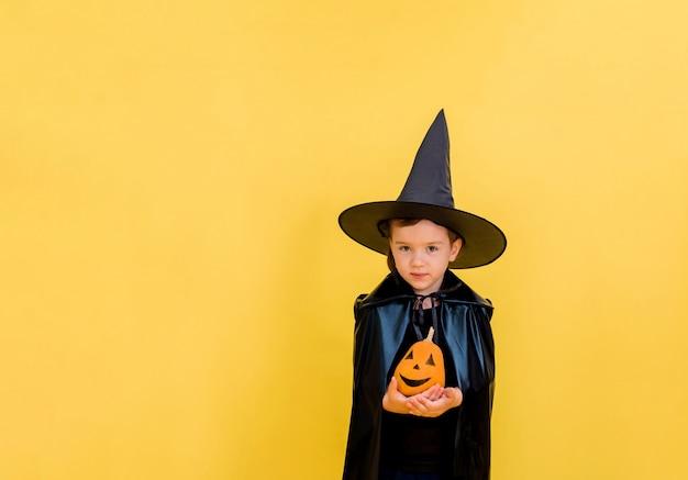 Mooie kleine heks in een hoed met een versierde pompoen op een geel geïsoleerd
