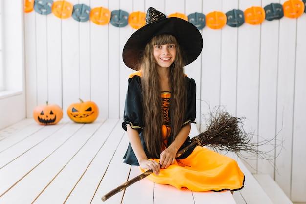Mooie kleine heks met bezem op halloween-feest