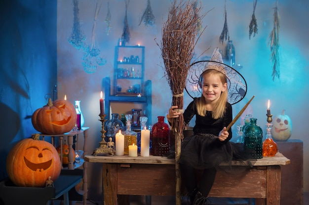 Mooie kleine heks met halloween-versieringen