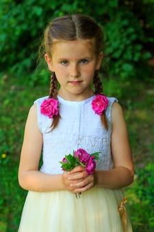 Mooie kleine jonge baby met bloemen in hun handen in de zomer park.