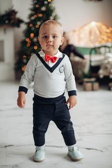 Mooie kleine jongen in een pak loopt thuis naar de huiskamer