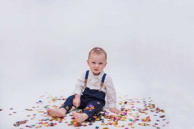 Mooie kleine jongen in een wit overhemd en een blauwe broek zit met confetti