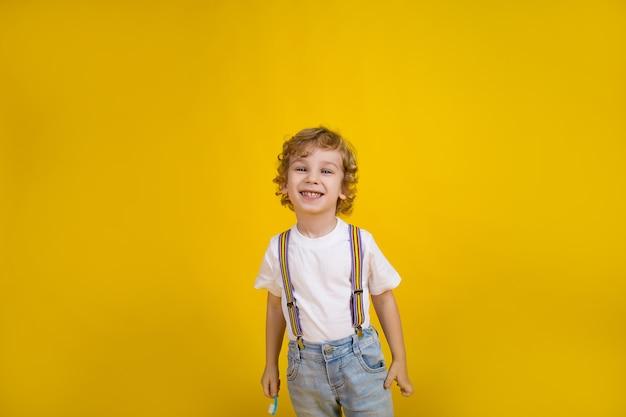 Mooie kleine jongen met krullend haar op een gele achtergrond staat met een tandenborstel glimlachend