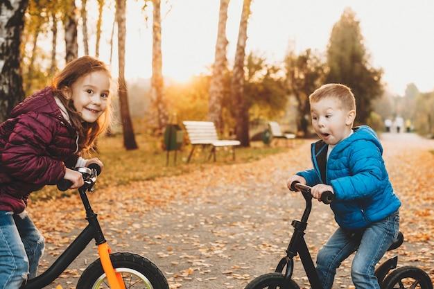 Mooie kleine jongen met plezier met zijn zus zittend op hun fietsen otudor in het park van aangezicht tot aangezicht.