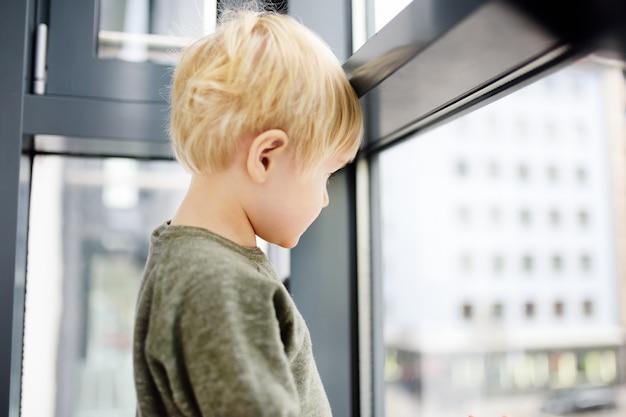 Mooie kleine jongenszitting op het venster dichtbij panoramisch venster en buitenkant het kijken