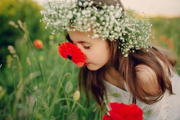 Mooie kleine meisje ruiken een papaver